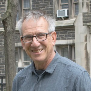 A man, wearing glasses, stand in front of a building with a Gothic facade, smiling into the camera.